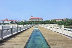 在一个码头的走道有在背景,烟台,中国的大厦的 库存照片