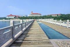 在一个码头的走道有在背景,烟台,中国的大厦的 免版税库存照片