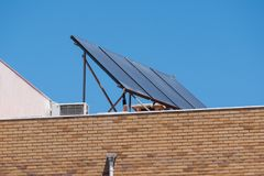 在一个砖公寓的屋顶的太阳电池板有蓝天背景 免版税库存图片