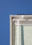 在一个砖墙上的新的雨天沟反对蓝天 库存图片