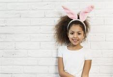 在一个砖墙的逗人喜爱的女孩有兔宝宝耳朵的 免版税库存照片