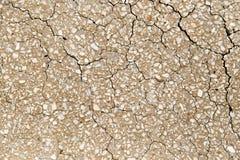 在一个破裂的混凝土墙的小小卵石作为背景 免版税库存图片