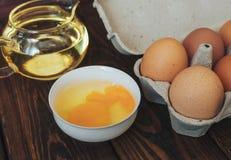 在一个碗、鸡蛋和向日葵油的残破的鸡蛋在一个玻璃容器 库存照片