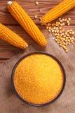 在一个碗、整个五谷和玉米棒的玉米少量在一张木桌上。 免版税库存图片
