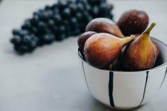 在一个碗和黑暗的葡萄的无花果在灰色背景 秋天harv 免版税库存照片