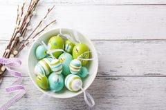 在一个碗有杨柳分支的和拷贝空间的五颜六色的复活节彩蛋在木背景 免版税图库摄影