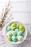在一个碗有杨柳分支的和拷贝空间的五颜六色的复活节彩蛋在木背景 库存图片