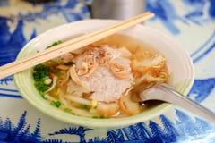 在一个碗的亚洲猪肉汤面有短的匙子和木cho的 库存照片