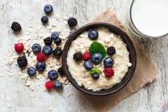 在一个碗的健康早餐燕麦粥粥有杯的牛奶 免版税图库摄影