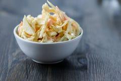 在一个碗的凉拌卷心菜在一张木桌上 免版税库存照片