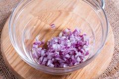 在一个碗的切的红洋葱在桌上 免版税图库摄影
