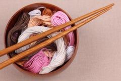 在一个碗的十字绣螺纹有筷子的 免版税库存图片