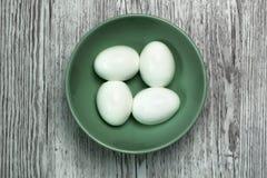 在一个碗的四个熟蛋在一张灰色木顶视图 免版税库存图片