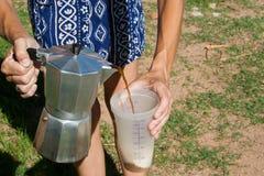 在一个碗的妇女倾吐的咖啡有Moka罐的 免版税库存照片