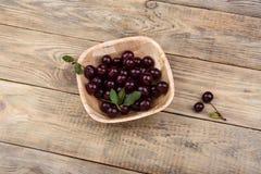 在一个碗的成熟樱桃在一张木桌上 库存图片