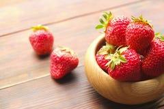在一个碗的成熟草莓木表面,春天/夏天上,绿色树离开背景 库存图片