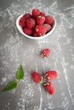 在一个碗的成熟莓在与驱散的一张灰色石桌上 免版税库存照片