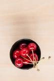 在一个碗的新鲜的樱桃在桌上 免版税图库摄影