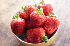 在一个碗的新鲜的草莓在一张木桌上 在一个碗的新鲜的草莓在一张木桌上 素食主义,素食主义者 免版税库存图片
