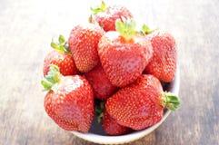 在一个碗的新鲜的草莓在一张木桌上 在一个碗的新鲜的草莓在一张木桌上 素食主义,素食主义者 库存照片