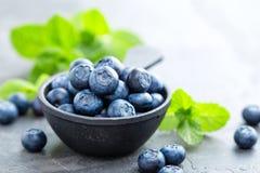 在一个碗的新鲜的蓝莓在黑暗的背景,顶视图 水多的野生森林莓果,越桔 免版税库存照片