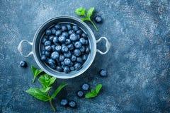 在一个碗的新鲜的蓝莓在黑暗的背景,顶视图 水多的野生森林莓果,越桔 库存照片