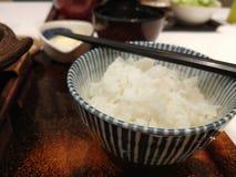 在一个碗的日本米用在上面的剁棍子 免版税库存图片