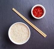 在一个碗的未加工的印度大米有chillie剥落和竹筷子的在石桌上 库存照片