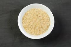 在一个碗的未加工的米在深黑色背景 免版税库存图片