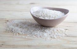 在一个碗的未煮过的米在木桌上 免版税库存照片