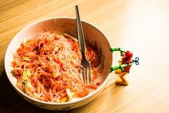 在一个碗的油煎的面条桃红色和一个小机器人 免版税库存图片