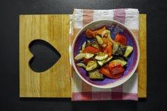 在一个碗的烤菜在木厨房上 免版税库存照片