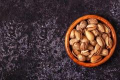 在一个碗的盐味的开心果在石背景 免版税库存图片