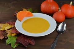 在一个碗的秋季南瓜汤用北海道南瓜、叶子和一把匙子在一张棕色木桌上 图库摄影