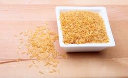 在一个碗的米在木背景 为烹调准备 图库摄影