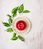 在一个碗的红色苹果有在白色木背景的叶子的 免版税图库摄影