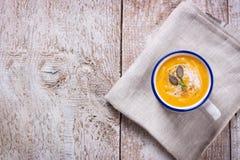 在一个碗的自创鲜美乳脂状的南瓜汤纯汁浓汤在木背景 免版税库存照片