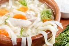 在一个碗的自创鸡汤面在有盐瓶和莳萝的一个木切板 免版税图库摄影