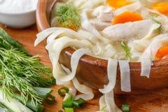 在一个碗的自创鸡汤面在有盐瓶和莳萝的一个木切板 库存图片