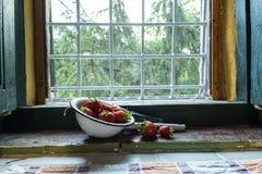 在一个碗的草莓在窗口附近的金属, 免版税库存图片