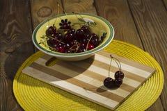 在一个碗的莓果樱桃在木背景 库存图片