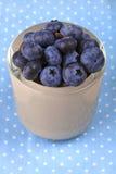在一个碗的蓝莓在蓝色加点了布料 免版税库存图片