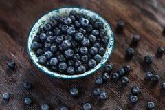 在一个碗的蓝莓在黑暗的土气木ta 免版税库存照片
