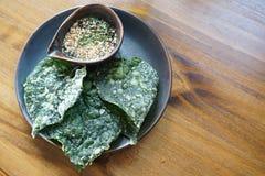在一个碗的酥脆叶子在木桌上 免版税库存图片