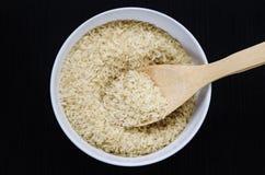 在一个碗的金黄米有在黑暗的桌上的匙子的 免版税库存照片