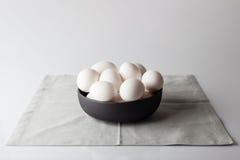 在一个碗的鸡蛋在从边的米黄餐巾 图库摄影
