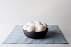 在一个碗的鸡蛋在从边的蓝色餐巾 图库摄影