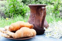 在一个碗立场的新月形面包在水罐和白花附近的一张桌上 库存图片