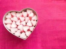 在一个礼物盒的桃红色蛋白软糖以心脏的形式在纺织品背景的,礼物的许多心脏蛋白软糖,甜点 免版税库存照片