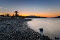 在一个离开的多岩石的海滩的清楚的天空在黄昏 库存图片